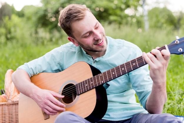 幸せな男がギターを弾く