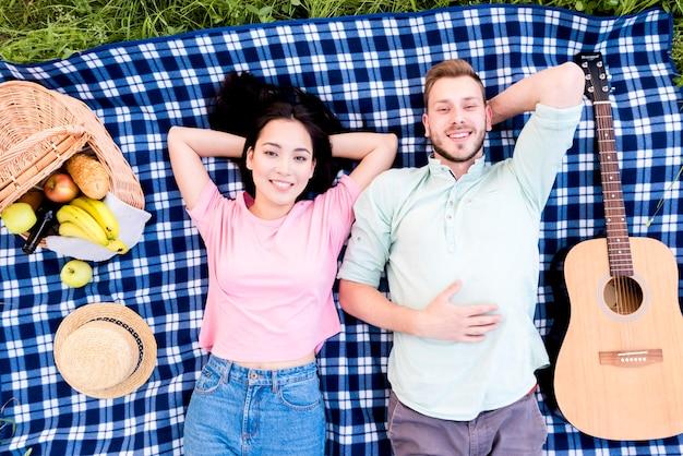 ピクニック格子縞の上に横たわるカップル