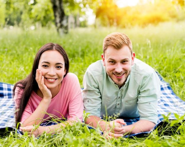 ピクニックにポーズをとって幸せな多民族カップル
