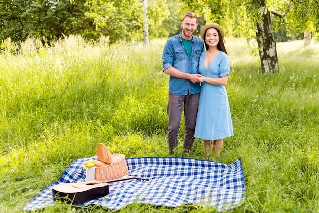 日当たりの良い牧草地の上に立って手を取り合って幸せな夢中のカップル