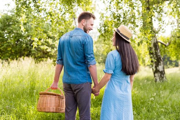 Счастливые улыбающиеся пара в любви, взявшись за руки в парке