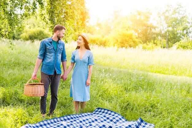 田舎で手を繋いでいる格子縞格子縞のそばに立つうっとりカップル