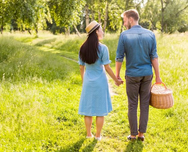 Влюбленная улыбающаяся пара стоит на дорожке парка, держась за руки
