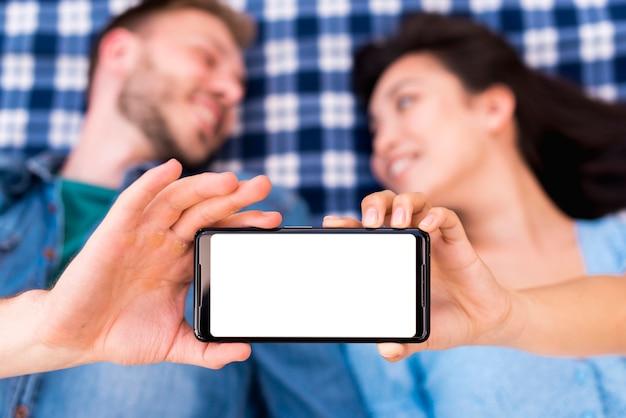 Молодая пара держит смартфон