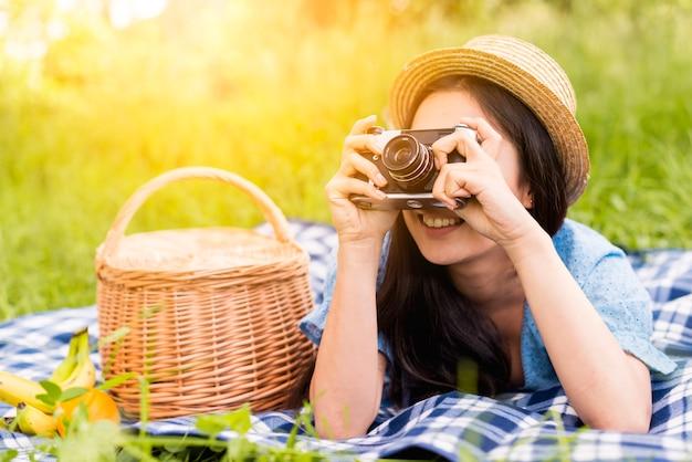 自然の中で写真を撮る若い陽気な女性