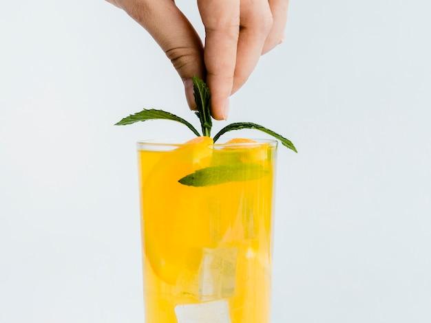 ミントの葉と飲み物を飾る手