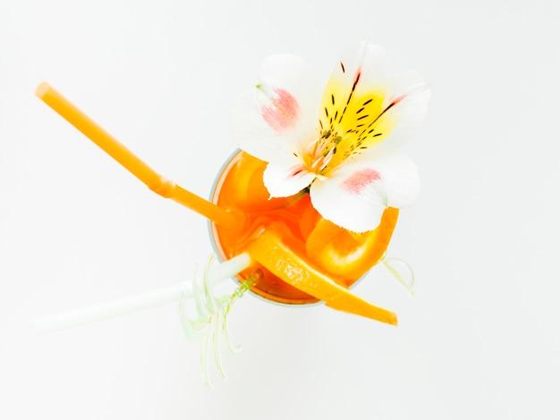 Стакан апельсинового коктейля с соломой и орхидеей