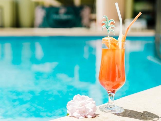 プールのそばのオレンジ冷たいカクテル