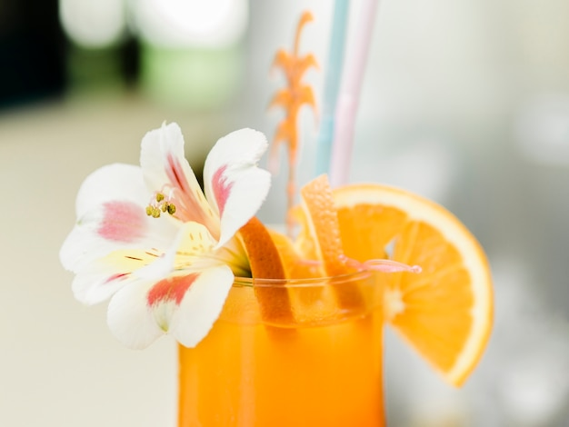 オレンジ色の蘭の花で飾られたフルーツカクテル