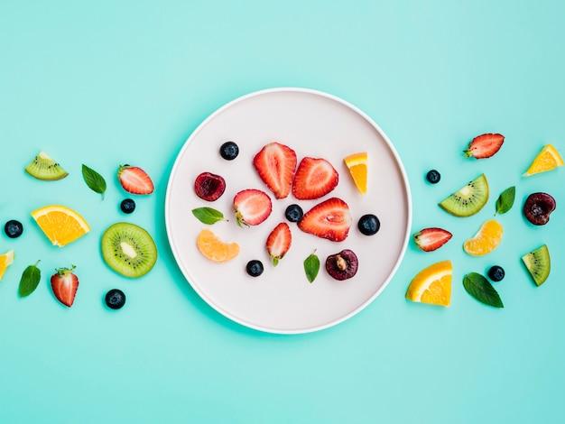 ターコイズブルーの背景に白い皿の上のエキゾチックな甘いフルーツのスライス