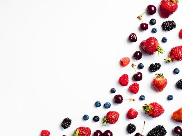 白い背景の右側に新鮮なおいしい果実のミックス