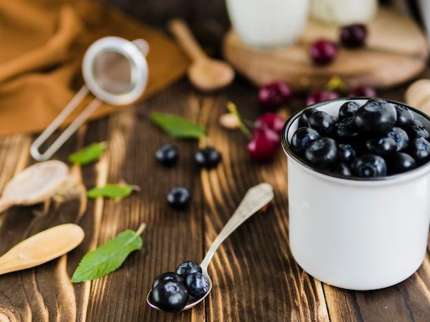 Сезонные ягоды черники в кружке на столе