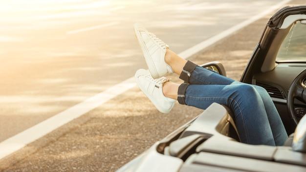 車からぶら下がっている女性の足