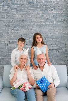 彼らの孫とパーティーハットを着て幸せな祖父母の肖像画