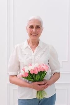 カメラ目線のチューリップの花の花束を保持している年配の女性のクローズアップ