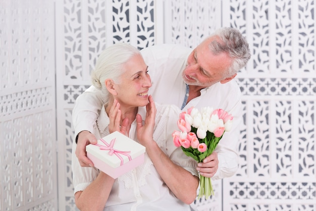 Счастливая старшая женщина получая удивленный подарок от ее любящего мужа