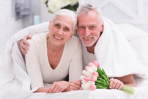 Портрет любящей старшей пары лежа на кровати с красивым цветочным букетом