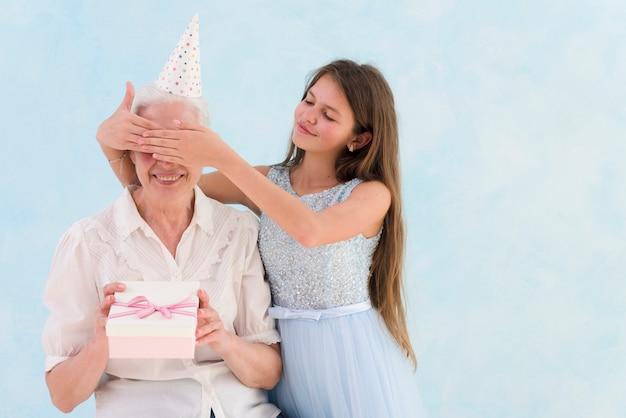 彼女の祖母の目を覆って驚いた贈り物をする美しい少女
