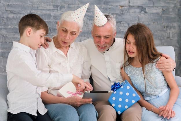 デジタルタブレットで彼の家族に何かを示す小さな男の子