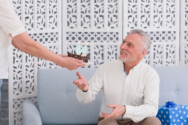 Крупным планом руки женщины, давая день рождения торт ее улыбающегося мужа