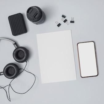 紙のシートと携帯電話を持つオフィスのデスクトップ