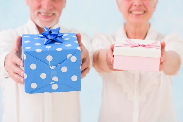 笑顔の夫と妻の誕生日ギフトボックスを与えることのクローズアップ
