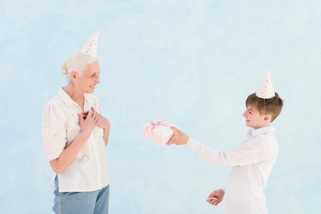 Улыбающийся мальчик дает подарок на день рождения своей бабушке на синем фоне