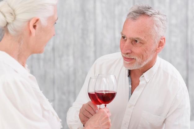 彼の妻を見ながらワイングラスをクリックしてシニアの笑みを浮かべて男