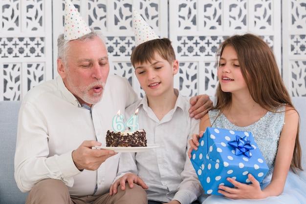 Дедушка дует на день рождения свечу со своими внуками