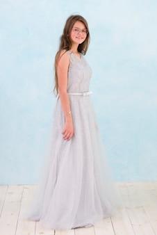 Вид спереди улыбающейся девушки в элегантном платье