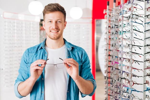 Мужчина ищет новые очки у оптометриста