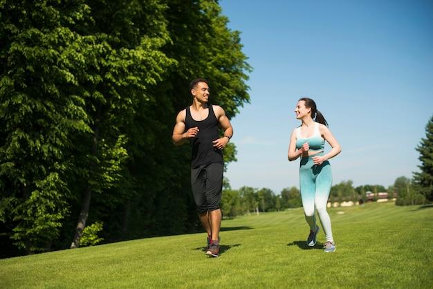 Мужчина и женщина бегут на открытом воздухе в парке