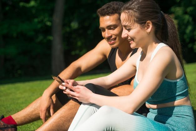 Мужчина и женщина, принимая селфи в парке