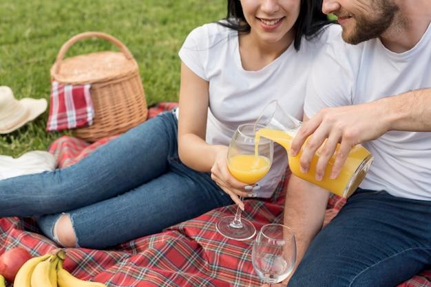 ピクニック毛布にオレンジジュースを持っているカップル