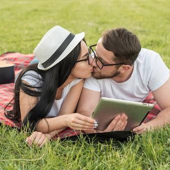 カップルがピクニック毛布にキス