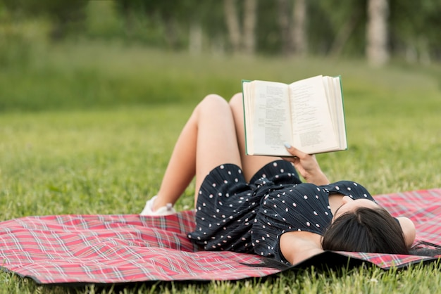 Девушка, читающая на одеяле для пикника