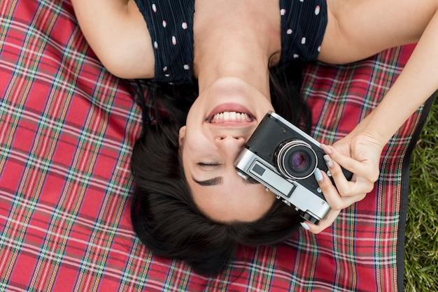 Девушка берет фото на одеяло для пикника