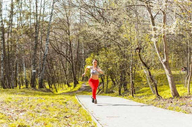 木を走っている若い女性