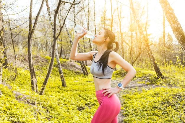 若い女性は自然の中で水を飲む