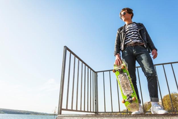 スケート公園で彼のスケートボードを持つ若者