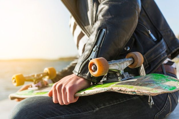 Молодой человек со скейтбордом у моря