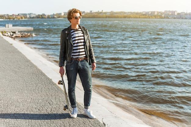海のそばのスケートボードを持つ若い男
