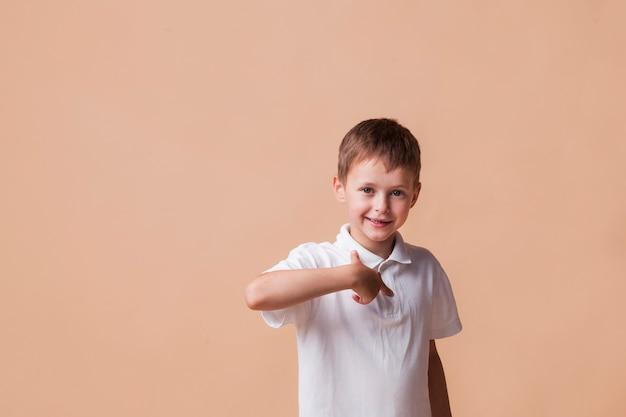 Счастливый мальчик, указывая пальцем на себя, стоя возле бежевой стены