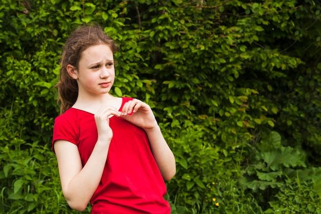 Портрет страшно девушки, стоя в парке