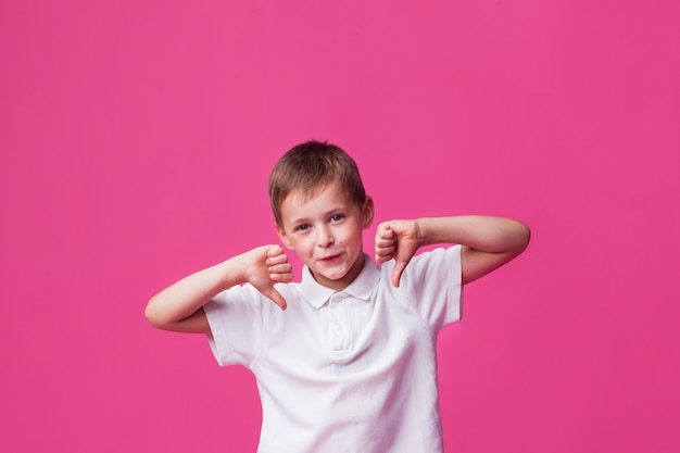 ピンクの壁の上の嫌いなジェスチャーを示す笑顔のかわいい男の子