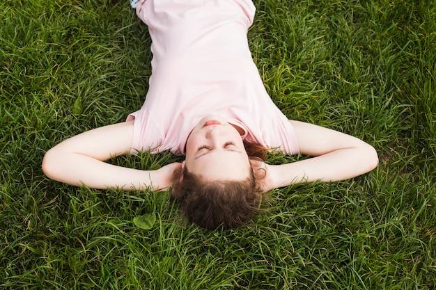 公園の芝生の上に横たわってかわいい女の子のオーバーヘッドビュー