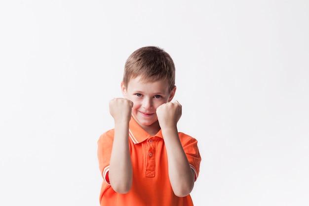 カメラを見て白い壁にイエスジェスチャーを作る拳を食いしばって笑顔の少年