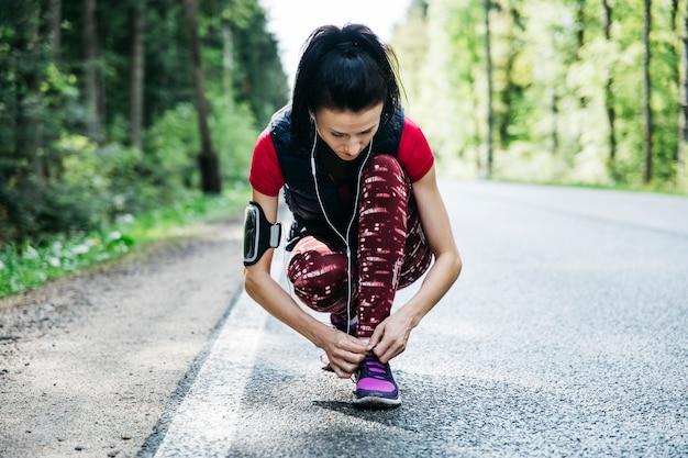 Женщина связывает кроссовки на дороге