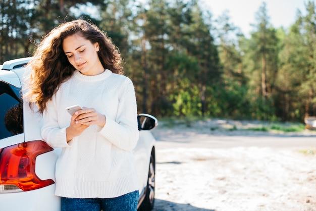 彼女の車の横にあるスマートフォンを持つ若い女