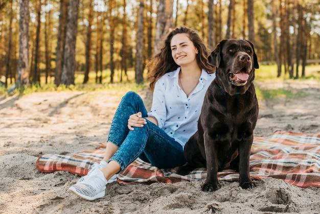 彼女の犬と一緒にピクニックをしている若い女性